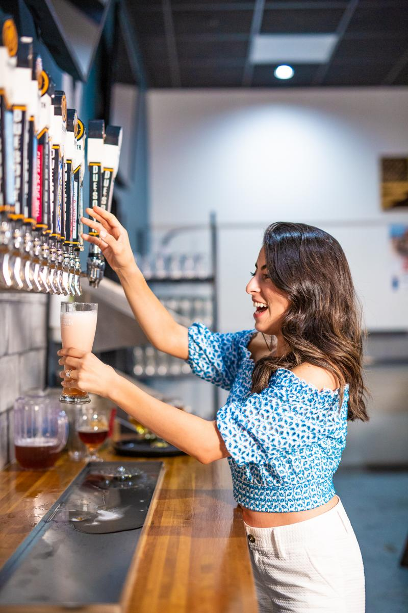Woman pouring beer from a tap at Due South Brewery.