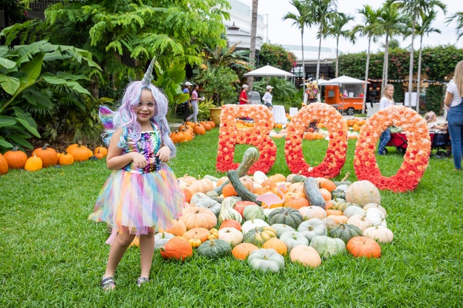 Girl dressed as unicorn in front of pumpkins