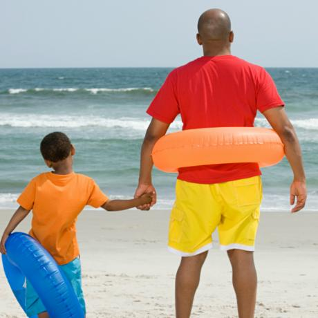 Father and son on beach with inner tubes