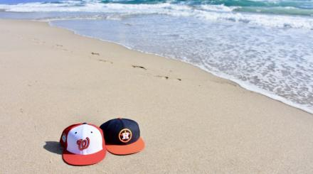 Houston Astros and Washington Nationals baseball caps in the sand at the beach