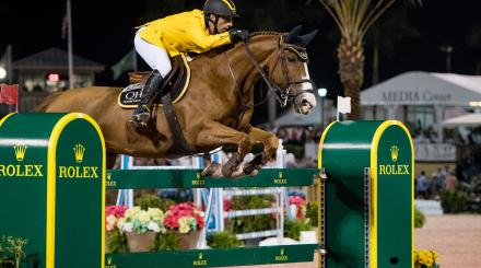 A rider jumping a horse over a competition barrier