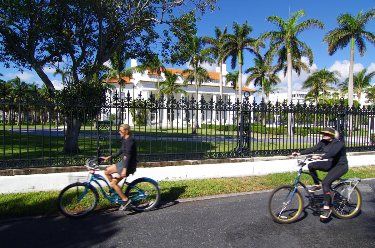 Cyclists ride in front of Flagler Museum