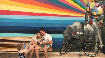 Family posing for toddler in front of a colorful Einstein mural