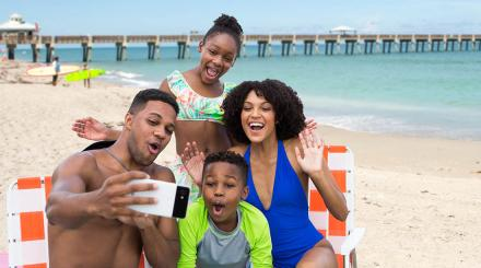Family of four in beach wear taking a group selfie at the beach