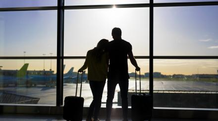 Silhouette couple in airport looking at planes